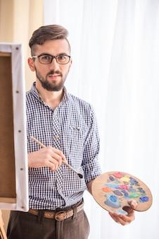 男性アーティストがイーゼルに絵を描き、パレットを保持しています。