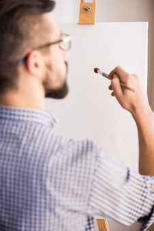 若い男の背面図は、空白のキャンバスに絵を描いています。