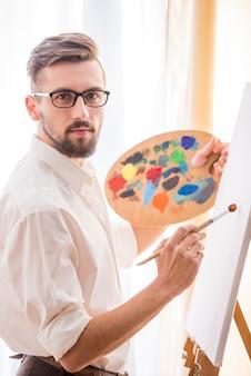 ブラシとパレットを持つアーティストが絵を描く