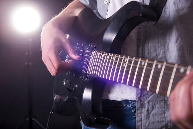 若い男のクローズアップ手はギターを弾いています。