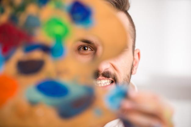 Крупный план молодого художника с палитрой