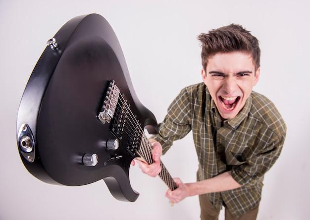 スタジオでエレクトリックギターを持つ若いギタリスト。