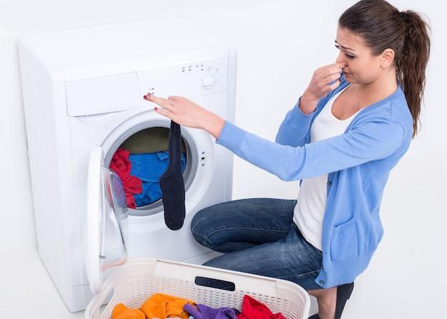 洗濯機の近くの女性は臭い靴下を保持しています。