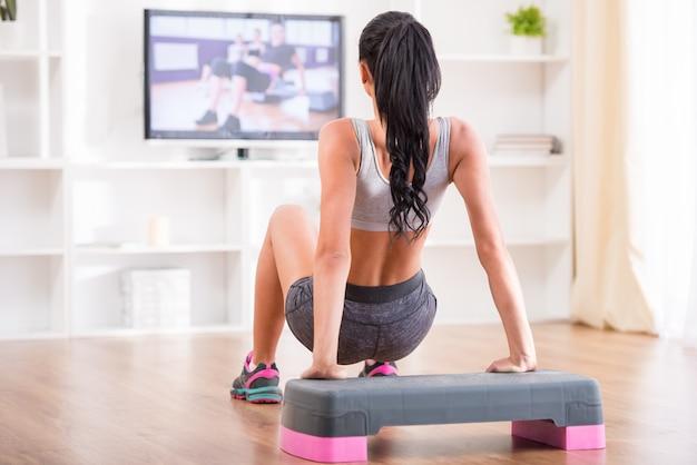 Женщина делает дома упражнения во время просмотра программы.