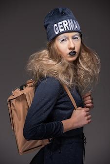 Девушка с рюкзаком стоит и позирует
