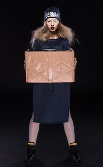 Девушка в черном наряде стоит с коробкой в руках.