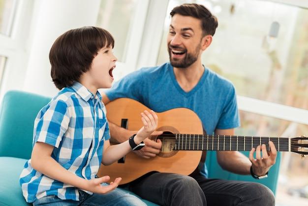 ひげを生やした若い父親が息子とギターを弾いています。