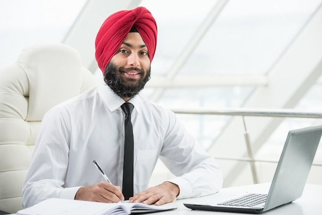 インドのビジネスマンは、オフィスで彼のコンピューターに取り組んでいます。