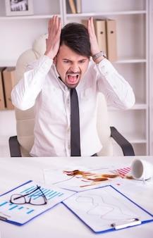 ドキュメントにこぼれたコーヒーに怒っているビジネスマン。