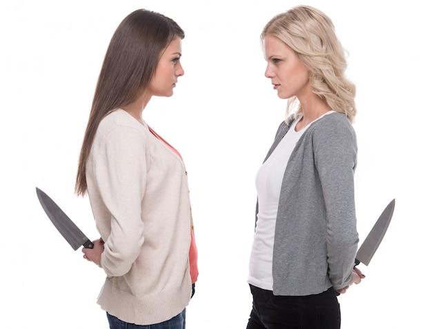 女性はお互いを見て、ナイフを持っています。