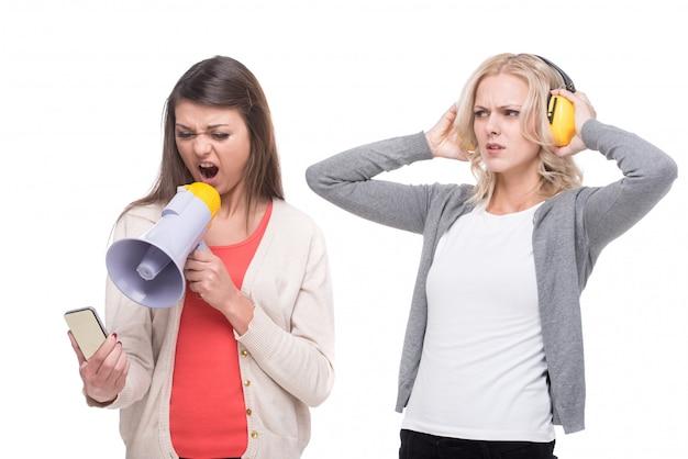 怒っている女性はメガホンを通して電話で叫んでいます。