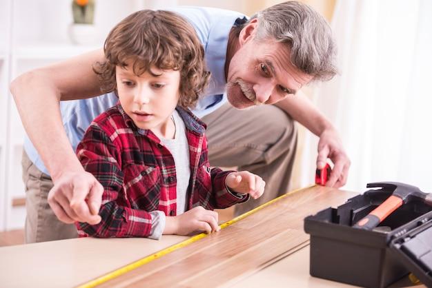 祖父と孫がテーブルを測定しています。