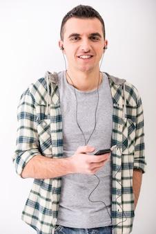 携帯電話とヘッドフォンを持つカジュアルな若い男。