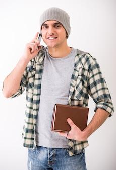 カジュアルな若い男は電話で話していると本を保持しています。