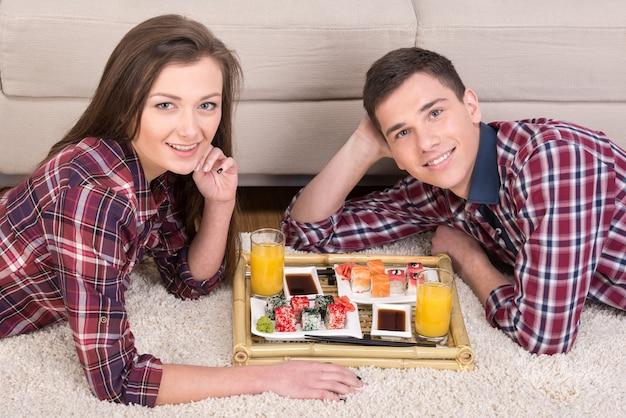 寿司と家の床に飲み物と若いカップル。