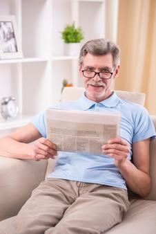 Старший мужчина читает газету у себя дома.