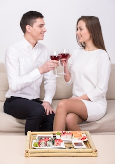 カップルは一緒に座って、寿司を食べて、ワインを飲みます。