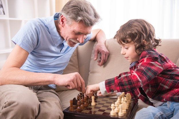 若い男の子は自宅で祖父とチェスをしています。