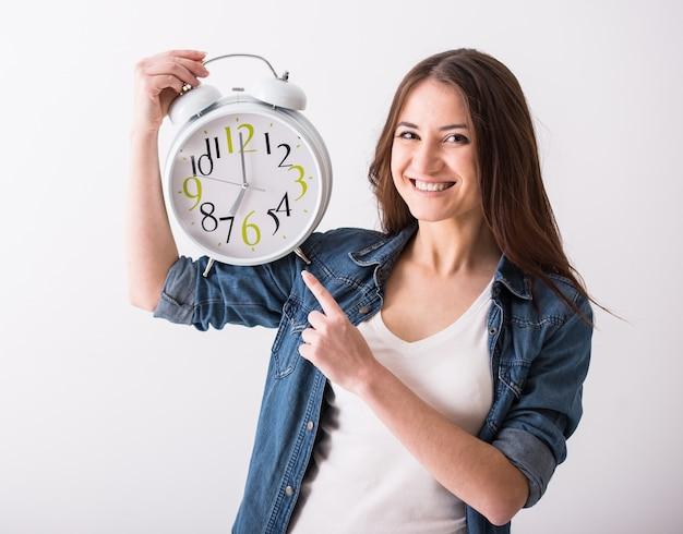 Понятие времени. молодая женщина улыбается держит часы.