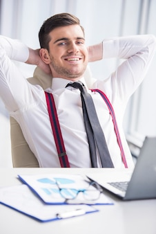 幸せな実業家は彼のオフィスでリラックスしています。