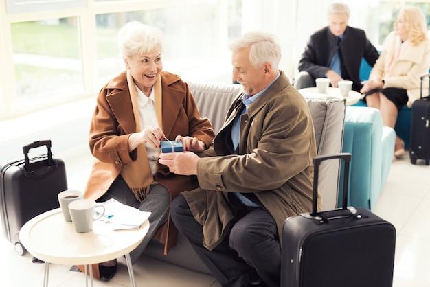 Пожилой мужчина делает неожиданный подарок пожилой женщине.