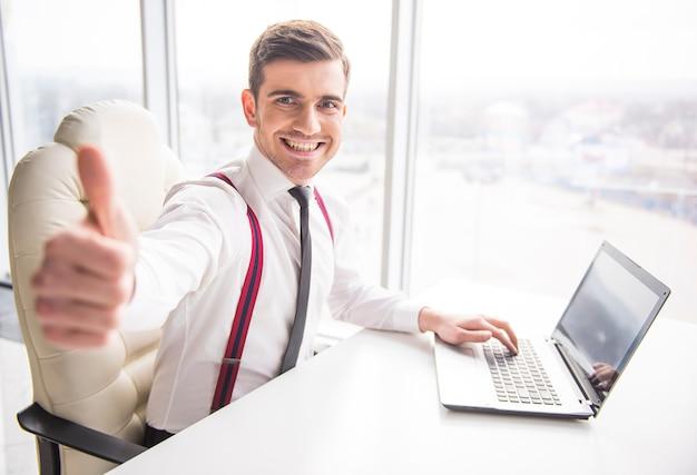 Молодой улыбающийся бизнесмен показывает палец вверх.