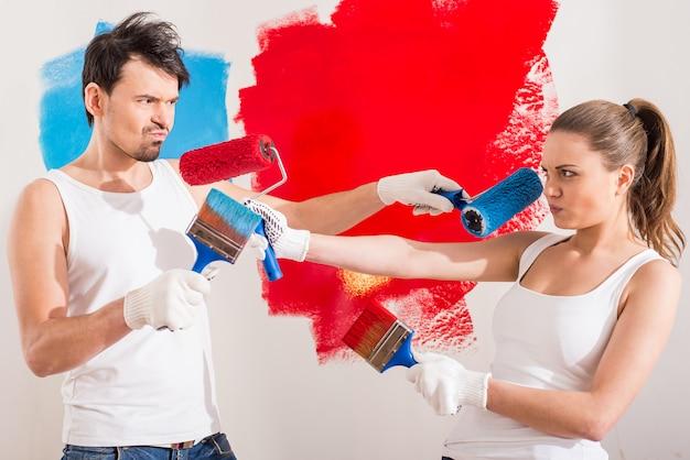 面白いカップルが自宅で修理をしています。