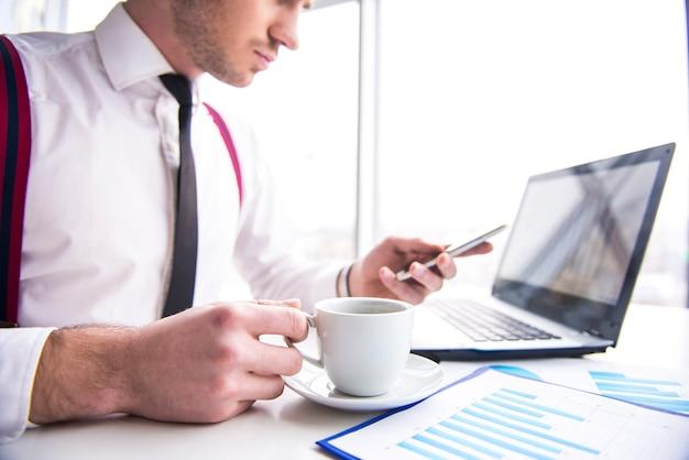 男はオフィスでラップトップで働いており、コーヒーを飲んでいます。