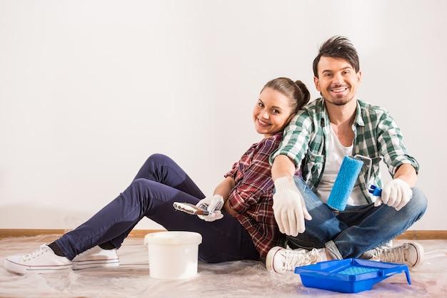 疲れた若いカップルがペイントブラシで床に座っています。