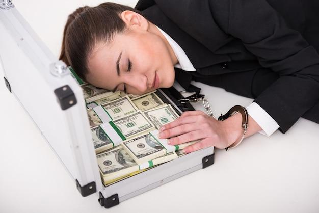 お金と手錠の完全なスーツケースを持つ若い女性。