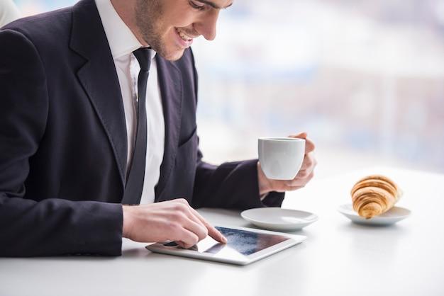 ビジネスマンはタブレットで作業し、コーヒーを飲みます。