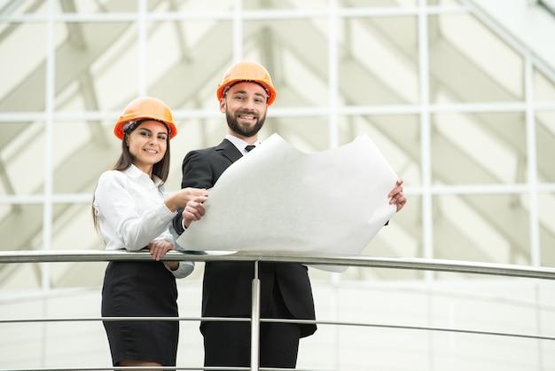近代的なオフィスの若い男性と女性の建築家。