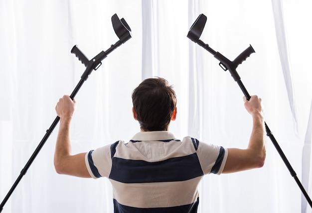 若い男の背面図は松葉杖を持ち上げています。