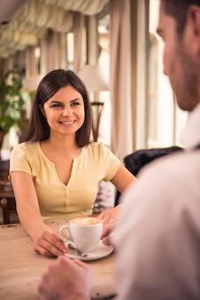 女と男がカフェでコーヒーを飲みます。