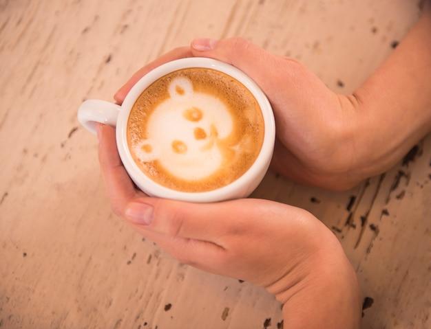 女性は写真と一緒に熱い一杯のコーヒーを保持しています。
