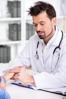 医師は、医療室で患者の血圧をチェックしています。