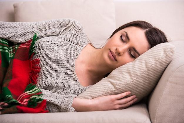 Привлекательная молодая самка спит на диване у себя дома.