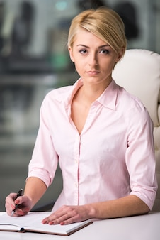 美しい若い女性の肖像画は、オフィスで働いています。
