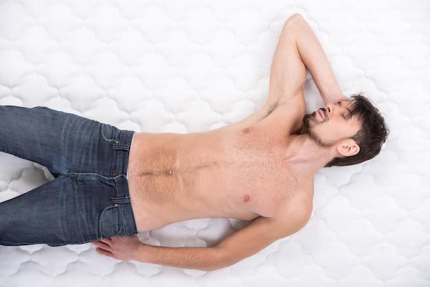 Молодой человек спит на матрасе.