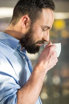 ガラスを通してコーヒーのカップを持つ男の側面図です。