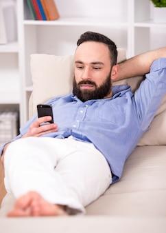 男はソファでリラックスし、携帯電話を見て