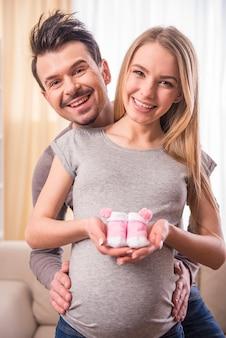男と妊娠中の妻はベビーソックスを試着しています。