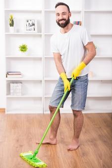 モップを持った男が家の床を洗い、笑顔を浮かべる。