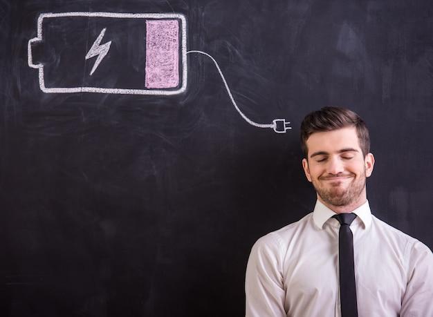 男は、バッテリーを引きながら黒板に立っています。