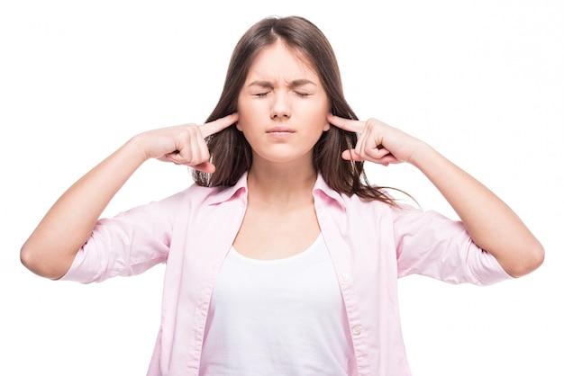 Девочка-подросток закрыла уши пальцами.