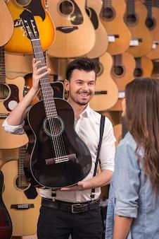 男は音楽店で女の子のギターに見せています。