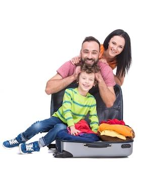 Счастливые веселые родители и их сын в чемодане.