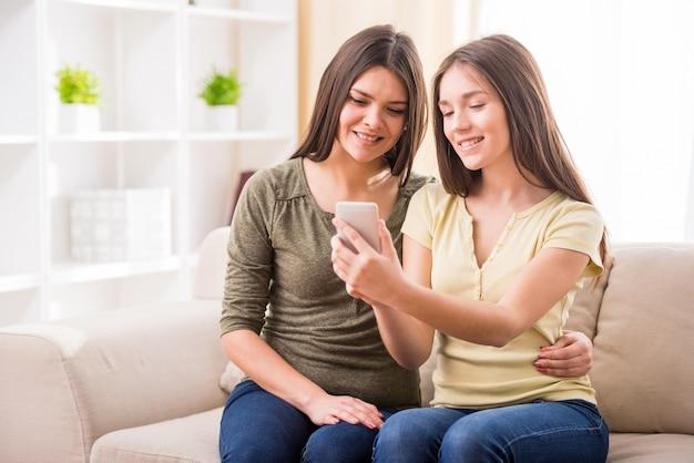 母と彼女のかわいい十代の娘は電話を見ています。