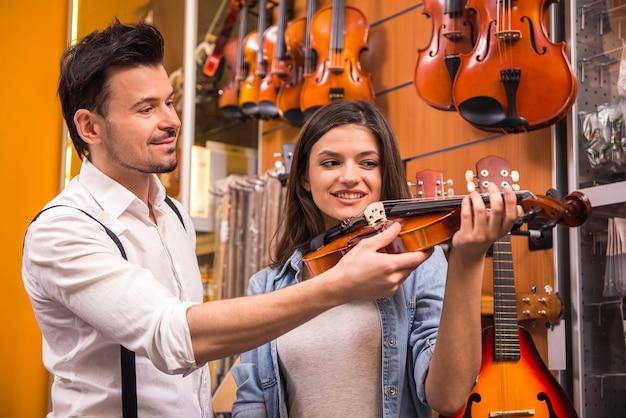男は少女に音楽店でバイオリンを弾くように教えています。