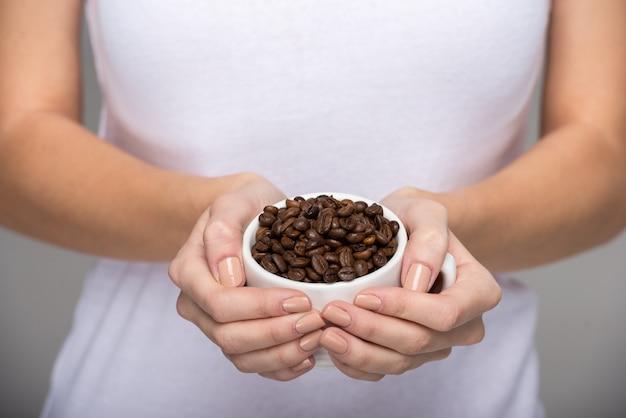 女性は一握りの焙煎コーヒー豆を見せています。